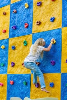 Een klein meisje klimt op een stenen muur in een kindercentrum