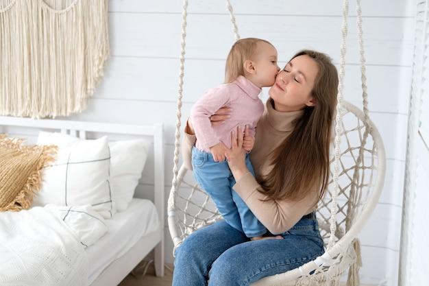 Een klein meisje kust haar moeder in de hangende stoel in hun slaapkamer lichte kamer in scandinavische stijl