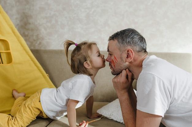 Een klein meisje kust haar vaders neus terwijl ze thuis op de bank speelt