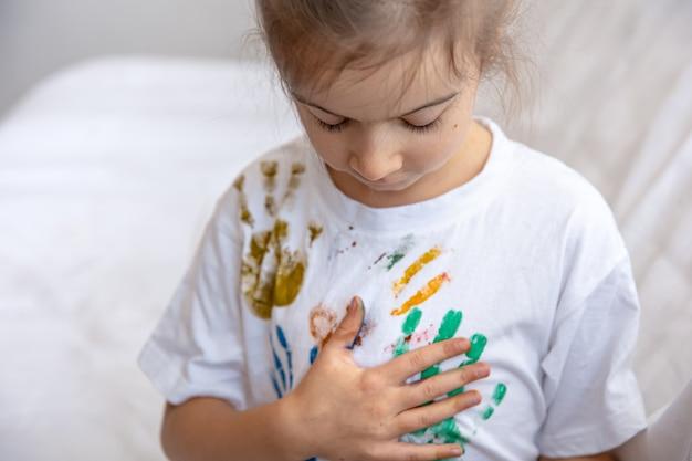 Een klein meisje laat sporen van geschilderde handpalmen achter op een t-shirt. creativiteit en kunst van kinderen.