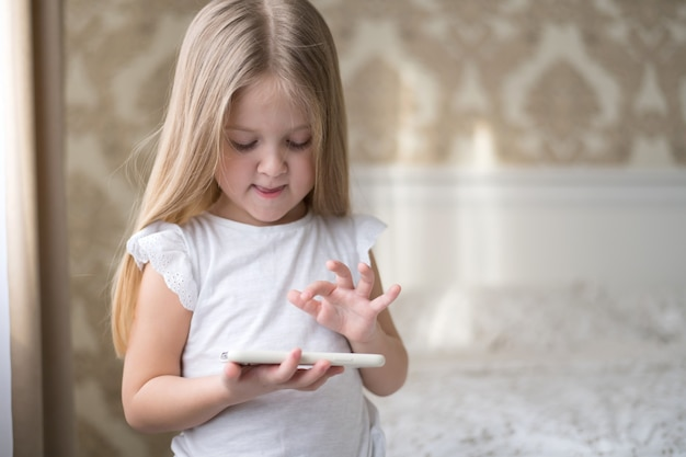Een klein meisje lacht en speelt aan de telefoon met slaapkamerachtergrond