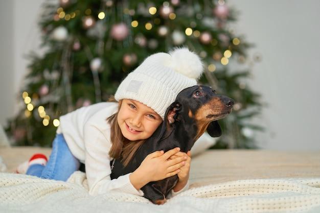 Een klein meisje lacht met haar vriend, een teckelhond, bij de kerstboom.