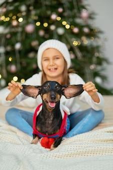Een klein meisje lacht met haar vriend, een teckelhond, bij de kerstboom