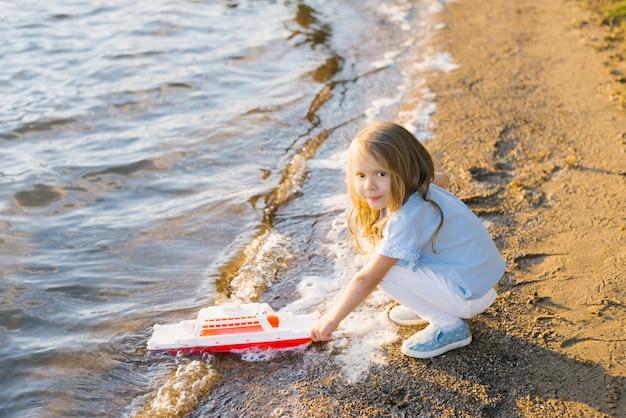 Een klein meisje lanceert een speelgoedboot in het meer