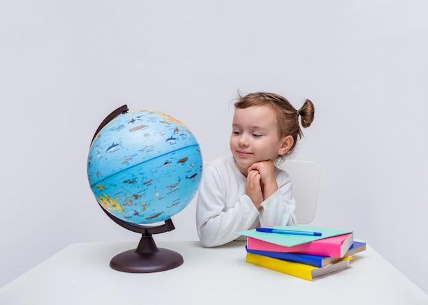 Een klein meisje leerling zit aan een tafel met een wereldbol en boeken en kijkt naar de camera op een wit geïsoleerd