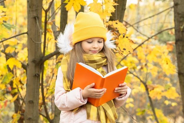 Een klein meisje leest een boek in het bos in de herfst.
