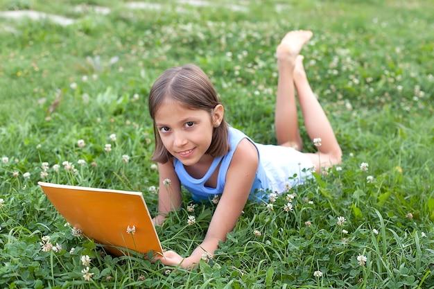 Een klein meisje leest op het gras. ze heeft een uitdrukking van plezier op haar gezicht en ze ziet er heel ontspannen uit. er is vrij veel open ruimte omheen.