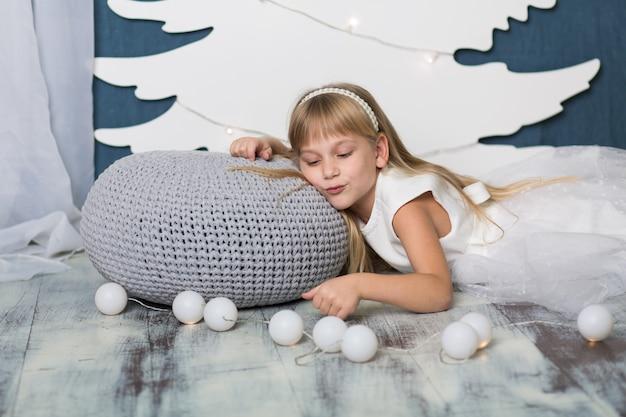 Een klein meisje ligt glimlachend op een kussen bedekt met een grijze gebreide deken, tegen de achtergrond van een kunstmatig wit kerstboomdecor van karton, en ernaast ligt een slinger