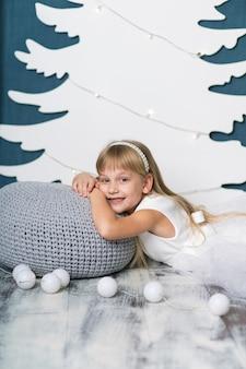 Een klein meisje ligt glimlachend op een kussen bedekt met een grijze gebreide deken