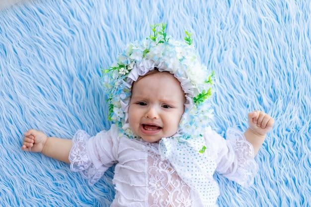 Een klein meisje ligt huilend op een blauw donzig kleed in een hoed gemaakt van bloemen