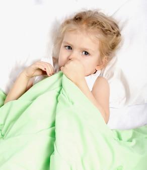 Een klein meisje ligt in bed onder een deken.