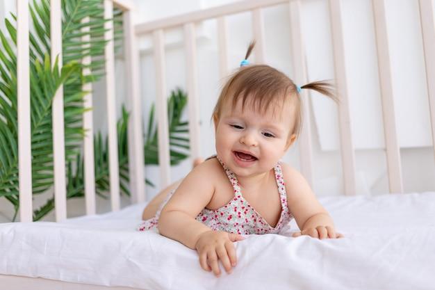 Een klein meisje ligt in een wieg in een lichte kamer te huilen Premium Foto