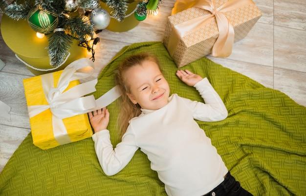 Een klein meisje ligt met cadeautjes op een groene gebreide deken onder de kerstboom en kneep in haar ogen