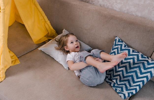 Een klein meisje ligt op de bank op haar rug met haar benen omhoog. spelletjes voor kinderen thuis. het concept van thuisgeluk