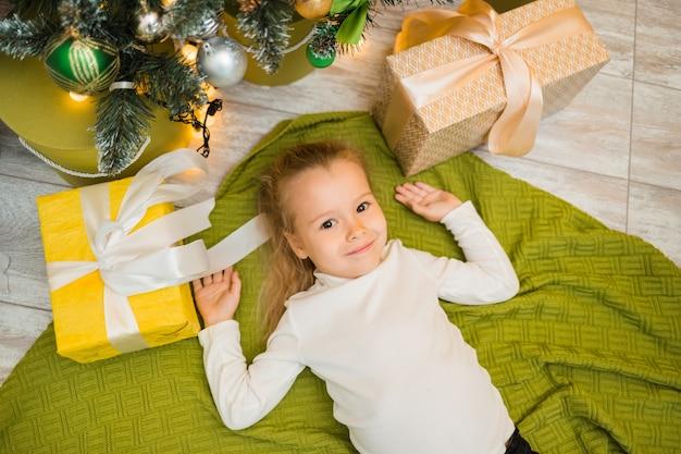 Een klein meisje ligt op een groene gebreide deken onder een kerstboom met cadeautjes