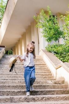 Een klein meisje loopt de trap op in het park en houdt een hoed in haar handen. het kind is blij en lacht. zomerse wandeling in de natuur of in de stad.