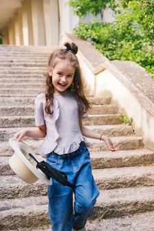 Een klein meisje loopt de trap op in het park en houdt een hoed in haar handen.