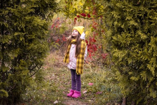 Een klein meisje loopt in het herfstpark.