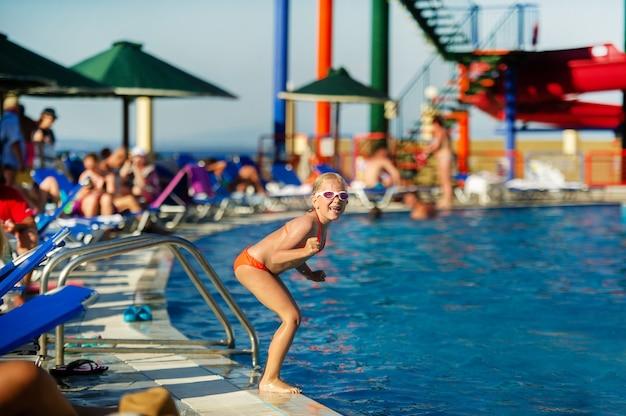 Een klein meisje maakt zich klaar om tijdens de zomervakantie in het zwembad van het waterpark te springen.