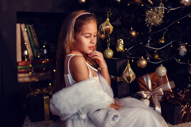 Een klein meisje met bruin haar op een donkere achtergrond in schattige jurk. goud en zwart. kerstboom en nieuwjaarsversieringen