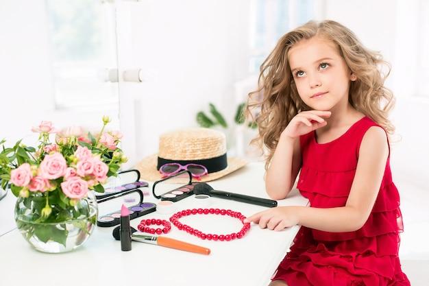 Een klein meisje met cosmetica. ze zit in de slaapkamer van moeder, bij de spiegel.