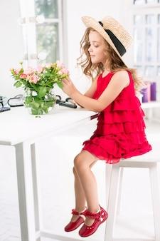 Een klein meisje met cosmetica zitten in de buurt van de spiegel.