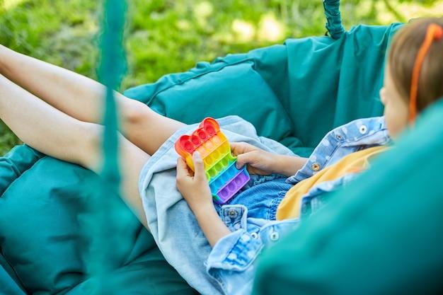 Een klein meisje met de hangende stoel buiten speelt pop it, kid hands spelen met kleurrijke pop it, fidget speelgoed in de achtertuin van het huis op een zonnige zomerdag, zomervakantie.