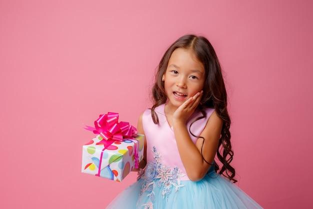 Een klein meisje met een aziatisch uiterlijk houdt een geschenk in haar handen om haar verjaardag te vieren