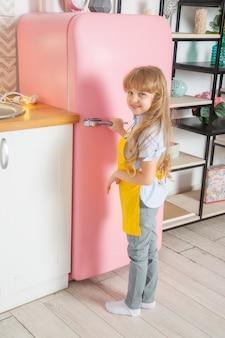 Een klein meisje met een blank uiterlijk, 7 jaar oud, opent de deur van een roze koelkast in een lichte scandinavische keuken