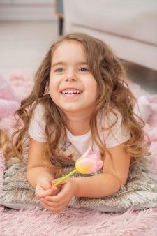 Een klein meisje met een blanke uitstraling ligt op de vloer in een lichte kamer in scandinavische stijl en lacht terwijl ze bloemen in haar hand houdt