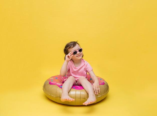 Een klein meisje met een bril zit in een cirkel. een ballon in de vorm van een donut. leuk meisje dat op een gele ruimte zonnebaadt.