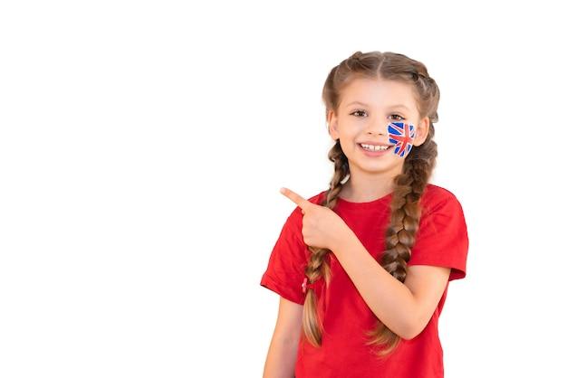 Een klein meisje met een britse vlag op haar wang wijst naar een onderwijsadvertentie.