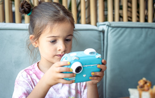 Een klein meisje met een digitale speelgoedcamera voor kinderen om direct foto's te printen.