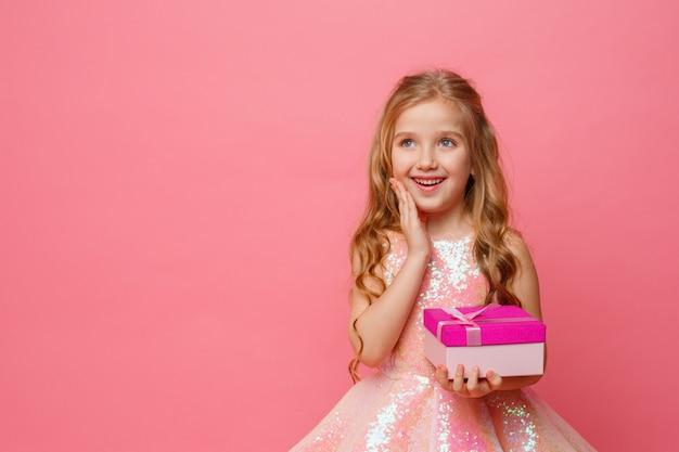 Een klein meisje met een geschenk in haar handen glimlacht op een roze ruimte.