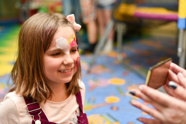 Een klein meisje met een geschilderd gezicht kijkt naar zichzelf in de spiegel op het feest