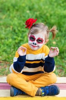 Een klein meisje met een geverfd gezicht, zittend op een bankje in lotushouding op de speelplaats, viert halloween of mexicaanse dag van de doden.