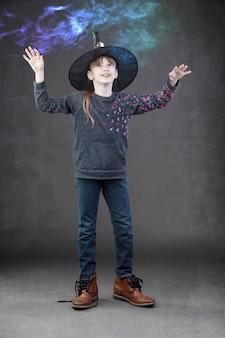 Een klein meisje met een hallowen-hoed kijkt naar gekleurde rook. kind voor halloween.