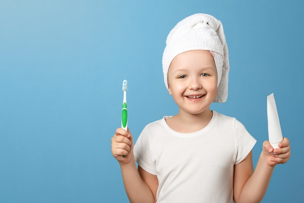 Een klein meisje met een handdoek op haar hoofd houdt een tandenborstel en tandpasta vast.