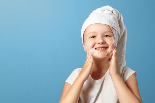 Een klein meisje met een handdoek op haar hoofd wast haar gezicht.