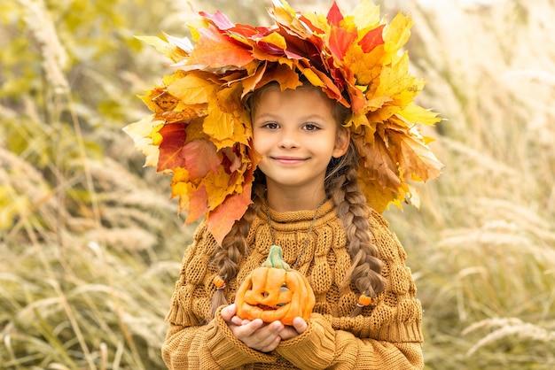 Een klein meisje met een herfstkrans op haar hoofd en een pompoen in haar handen.