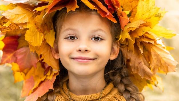 Een klein meisje met een herfstkrans op haar hoofd.