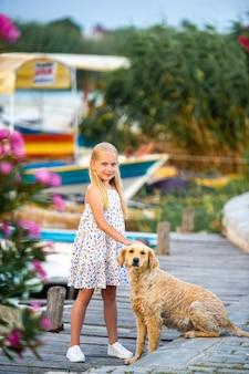 Een klein meisje met een hond aan de kade bij de rivier in een witte zomerjurk in de stad dalyan. kalkoen.