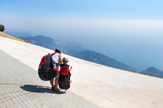 Een klein meisje met een instructeur in paragliding maakt zich op voor een vlucht vanaf de berg babadag.turkije