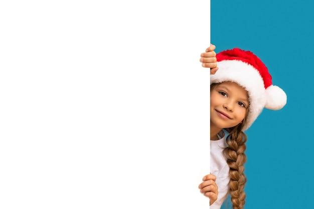 Een klein meisje met een kerstmuts kijkt uit achter een advertentie
