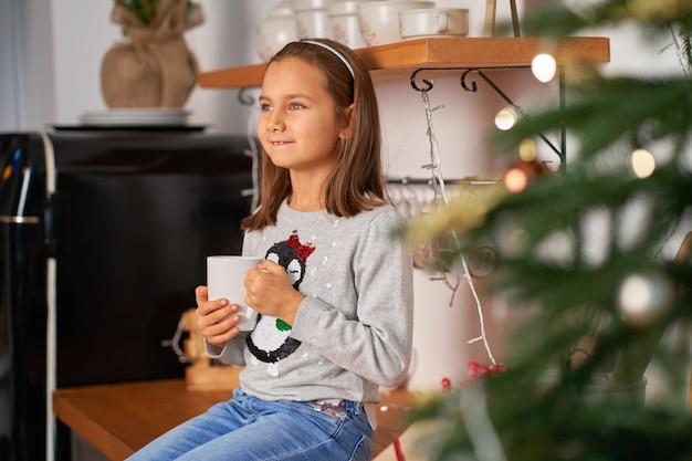 Een klein meisje met een kop hete thee droomt van een kerstcadeautje