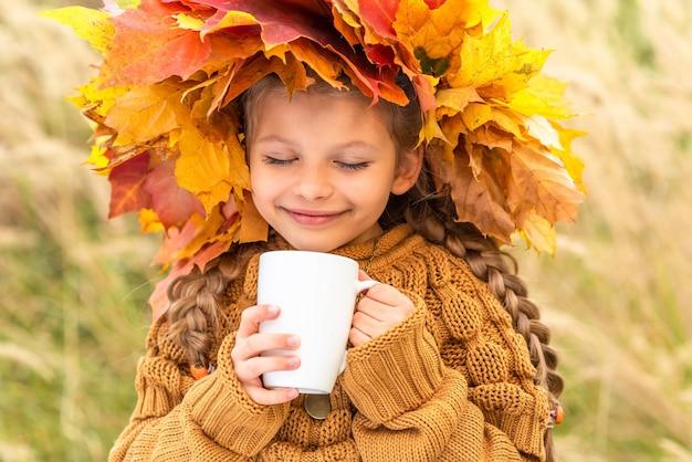 Een klein meisje met een krans op haar hoofd drinkt heerlijke thee in de herfst.