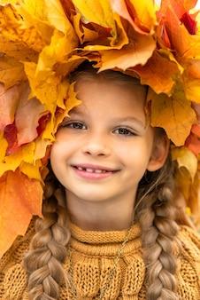 Een klein meisje met een krans van esdoornbladeren op haar hoofd.