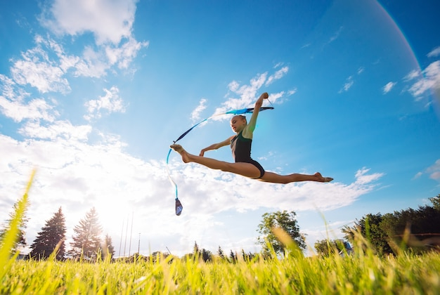 Een klein meisje met een lint dat op het gras springt.