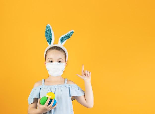 Een klein meisje met een medisch masker van coronavirus op haar gezicht, op haar hoofd met konijnenoren, houdt paaseieren in haar handen, wijst naar boven