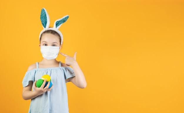 Een klein meisje met een medisch masker van coronavirus op haar gezicht, op haar hoofd met konijnenoren, houdt paaseieren van verschillende kleuren in haar handen